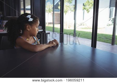 Thoughtful girl sitting at desk in school