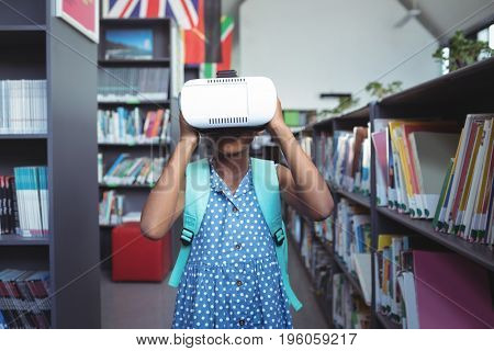 Girl wearing virtual reality simulator while standing bookshelf in library