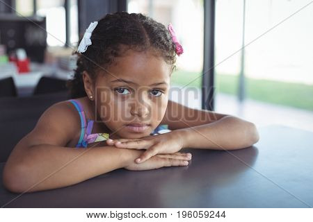 Close up portrait of girl leaning on desk in school
