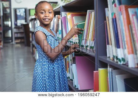 Portrait of girl selecting book from bookshelf in library