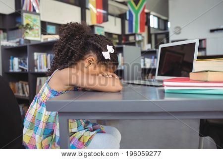 Side view of sad girl leaning on table in library