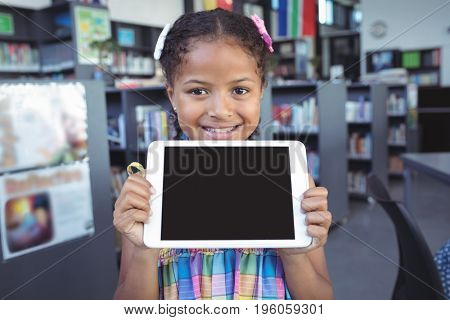 Portrait of smiling girl showing digital tablet in library