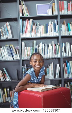 Portrait of smiling girl with book on ottoman against bookshelf in library