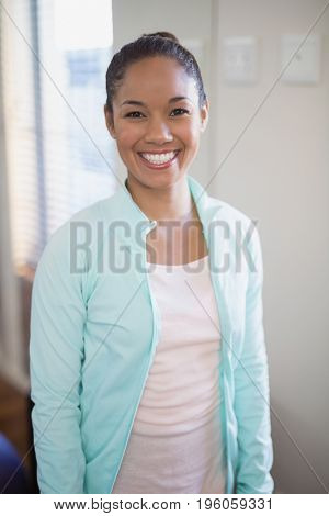 Portrait of smiling young female therapist standing at hospital ward