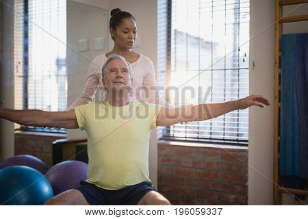 Female therapist looking at male patient sitting with arms outstretched at hospital ward