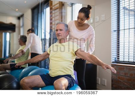 Female therapist looking at male patient exercising with arms outstretched at hospital ward