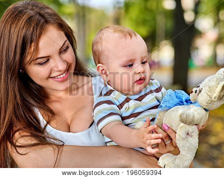 Baby in park outdoor. Kid with toy on mom's hands. Happy beautiful mom and child city park outside. Loving mother and her son spring outdoors. Child is very happy with new toy.