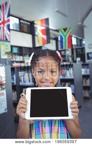 Portrait of smiling girl showing tablet computer in library