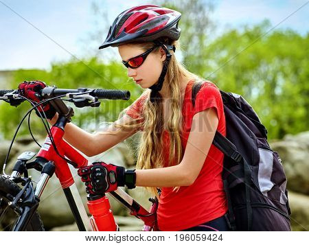 Woman on bicycle ride mountain. Girl traveling in summer park. Early morning with blue sky and clouds. Cycling person with rucksack. Sport trip is good for health. Healthy active lifestyle