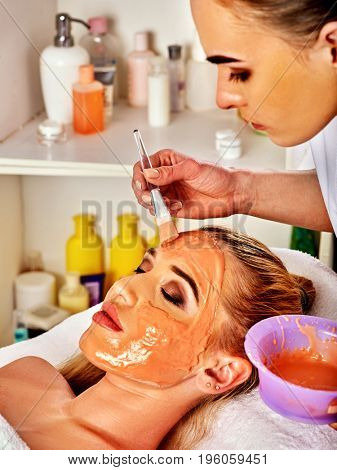 Collagen face mask . Facial skin treatment. Woman receiving cosmetic procedure in beauty salon. Bottle with moisturizing cream on background. Mask of honey, moisturizing the skin.