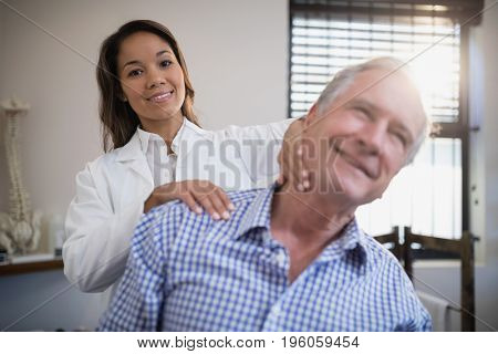 Portrait of smiling female therapist giving neck massage to senior patient at hospital ward