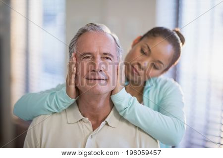 Female therapist holding head of senior male patient at hospital ward