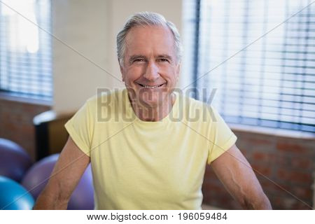 Portrait of smiling senior male patient against window at hospital ward