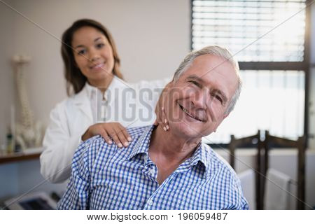 Portrait of smiling female therapist massaging neck at hospital ward