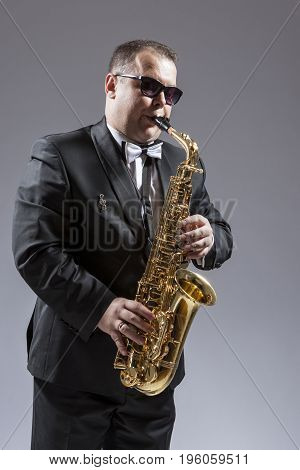 Music and Musicians Ideas and Concepts. Portrait of Caucasian Mature Saxophone Player in Sunglasses Playing the Instrument Against White. Vertical Orientation