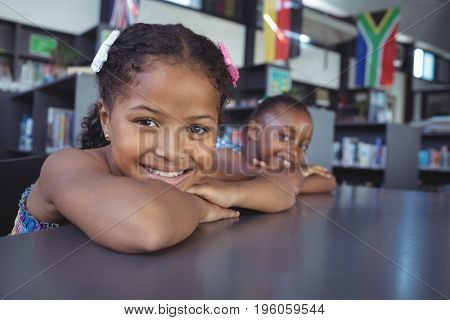 Close up portrait of smiling girls leaning on desk in library