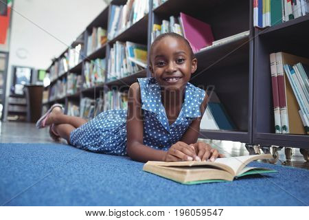 Portrait of smiling girl with book lying by shelf in library