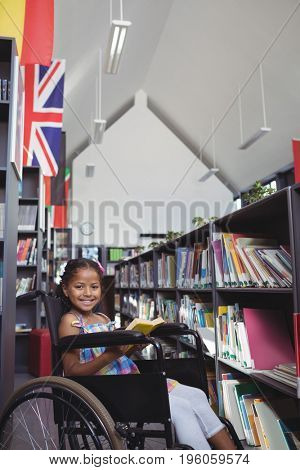 Portrait of smiling girl with book sitting on wheelchair by shelves in library
