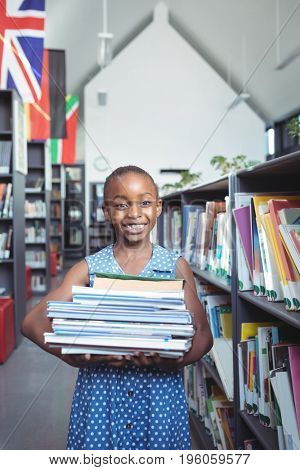 Portrait of smiling girl smiling while carrying books by shelf in library