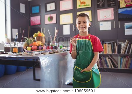 Portrait of smiling boy standing by desk in class at art studio