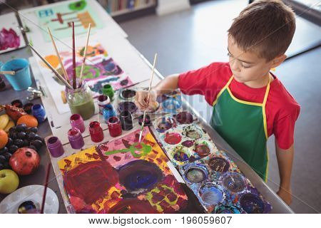 High angle view of boy painting at desk in class at art studio