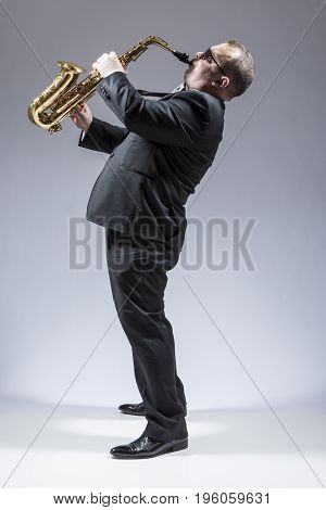 Music Ideas and Concepts. Portrait of Mature Caucasian Saxophone Player in Sunglasses Playing the Saxophone in Studio Environment. Vertical Image Composition