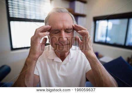 Senior male patient holding head during headache at hospital