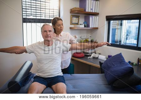 Female doctor examining male patient with arms outstretched at hospital ward