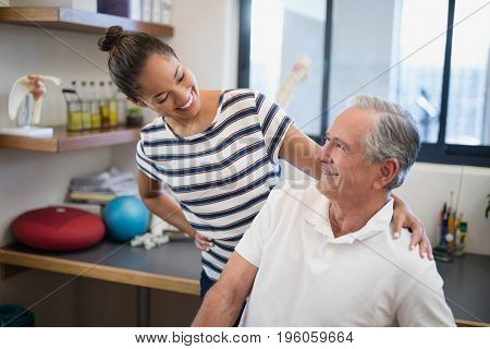 Smiling female doctor looking at senior patient at hospital ward