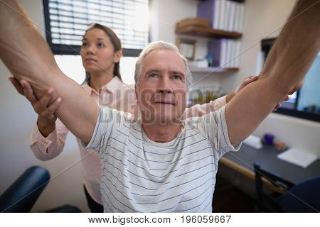 Male patient and female doctor with arms raised at hospital ward
