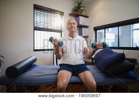 Senior male patient lifting dumbbells while sitting on bed at hospital ward