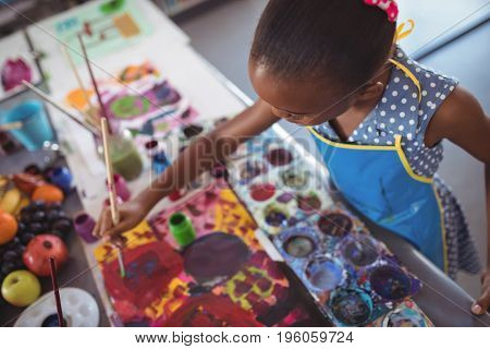 High angle view of focused elementary girl painting at desk in classroom