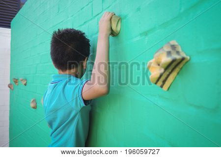 Side view of boy climbing green wall