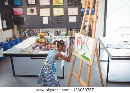 High angle view of focused girl painting on canvas in classroom