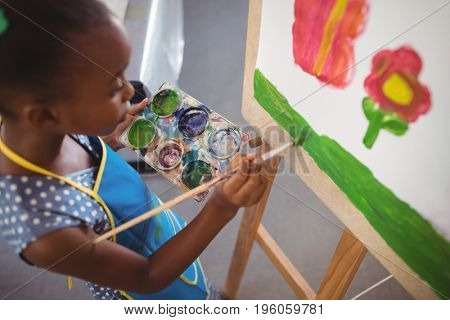 High angle view of elementary girl painting on canvas in classroom