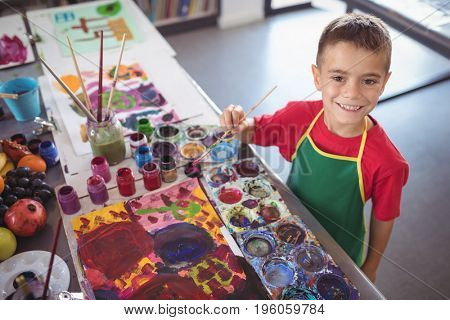 High angle portrait of boy painting at desk in class at art studio