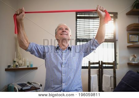 Smiling senior male patient pulling red resistance band while looking up at hospital ward