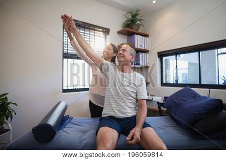 Smiling female doctor and male patient looking up with arms raised at hospital ward