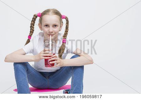 Kids Concepts. Little Caucasian Blond Girl Posing with Pink Pennyboard and Drinking Red Juice from Long Cup Using Straw. Against White. Horizontal Image Composition