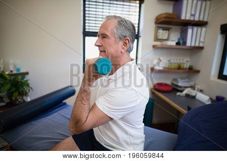 Side view of senior patient lifting dumbbell while sitting on bed at hospital ward