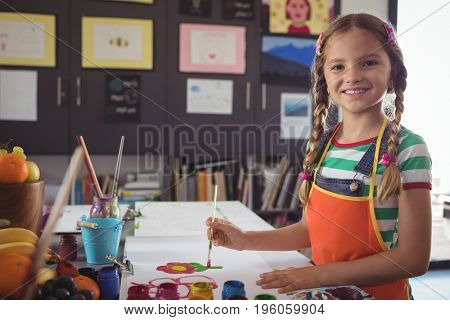 Portrait of smiling girl painting at desk in classroom