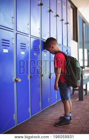 Side view of boy leaning on lockers in corridor at school