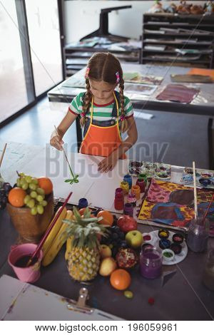 High angle view of girl painting on paper at desk in classroom
