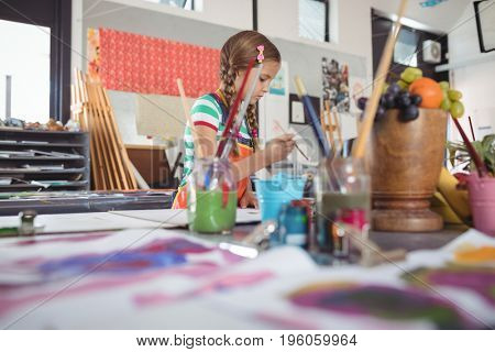 Girl painting in classroom at art school
