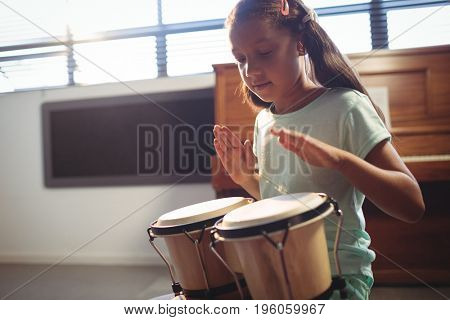 Girl playing bongo drums in classroom at music school