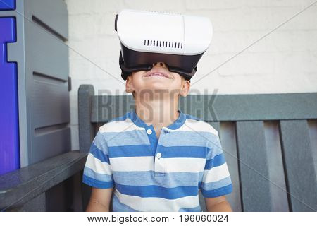 Boy watching virtual reality glasses while sitting on bench at school
