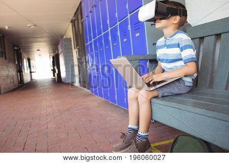 Boy using laptop and virtual reality glasses while sitting on bench by lockers in corridor at school