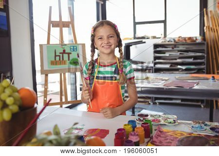 Portrait of happy girl holding paintbrushes while standing by desk at art classroom