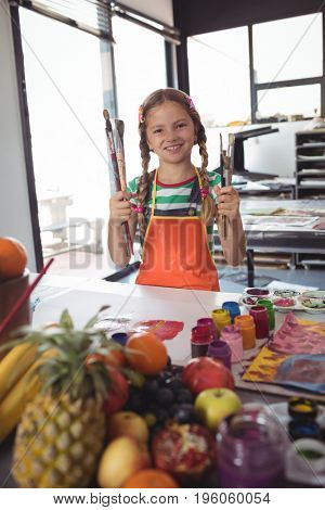 Portrait of smiling girl holding paintbrushes while standing by desk at art classroom