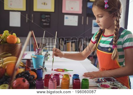Concentrated girl painting at desk in classroom